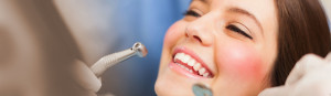 woman smiling while dentist inspects teeth